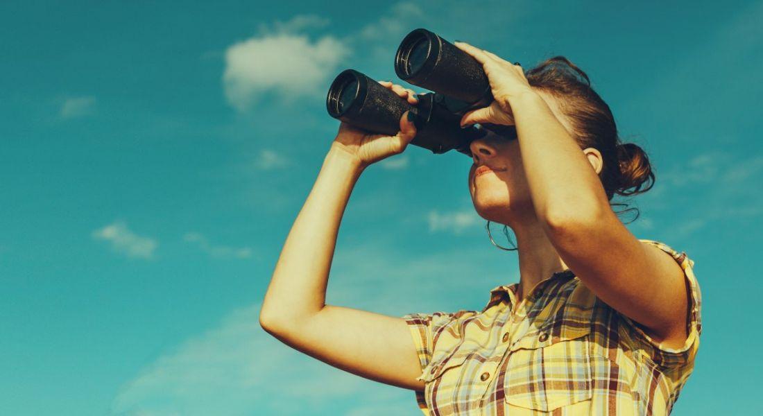 A woman looking through her binoculars against a blue sky.