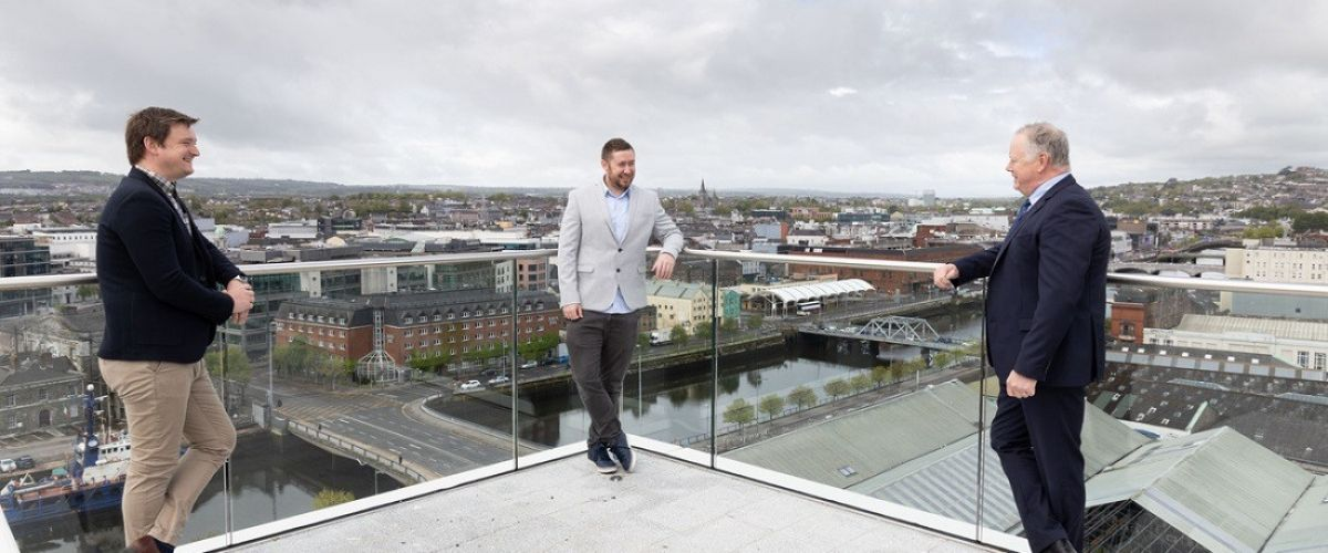Three men standing on a rooftop in Cork city.