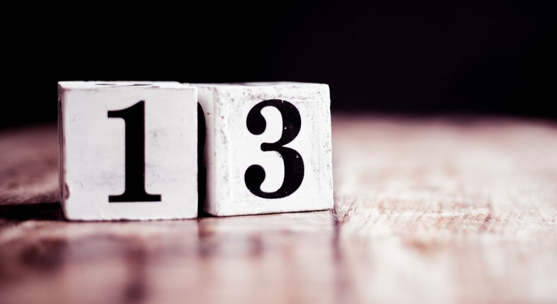 The number 13 written on two wooden blocks sitting on a table.