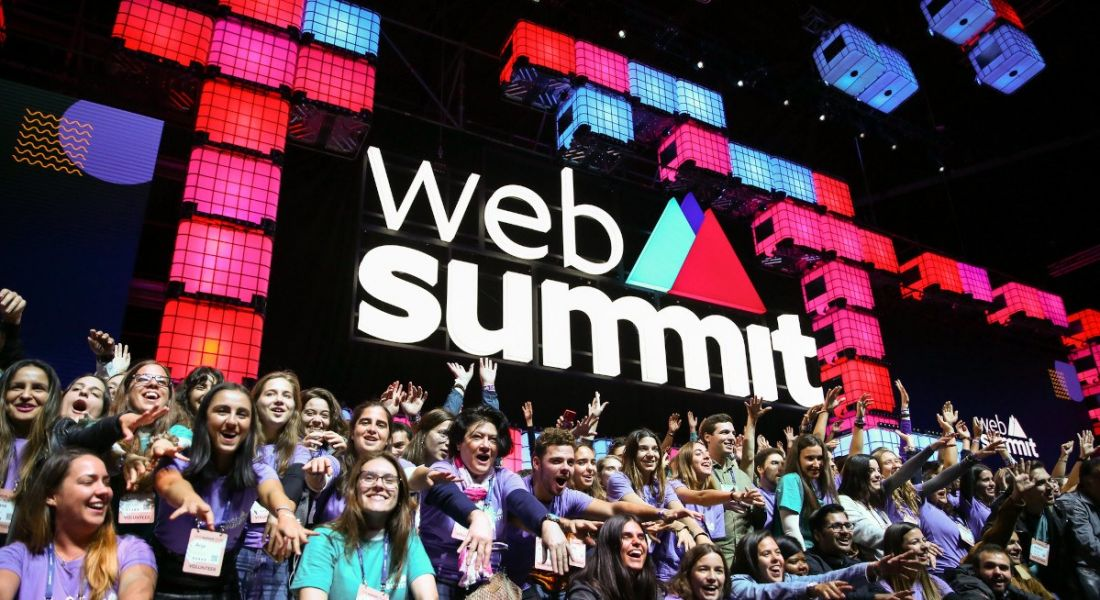 A crowd of people standing together and cheering on a stage decorated with the Web Summit logo and branding.