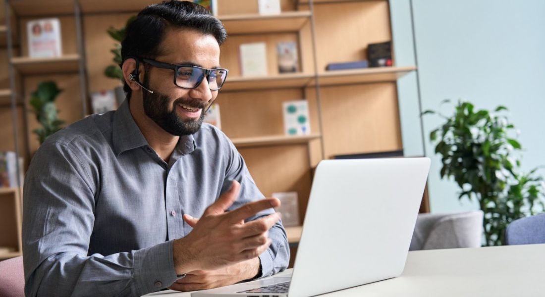 A man smiling working from home, sitting at a desk working on a laptop.
