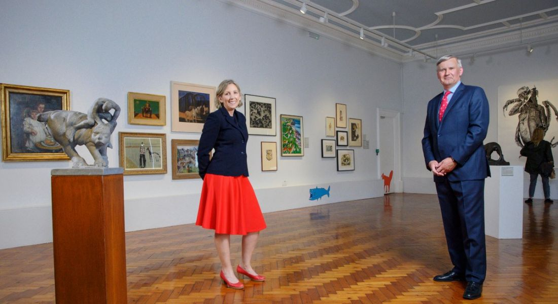 A woman and a man stand socially distanced in a gallery space containing many paintings and two sculptures on pedestals.