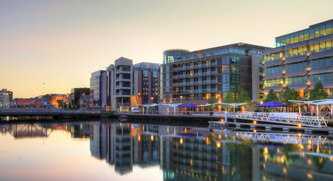 Buildings in Cork city lit up at dusk on the River Lee.