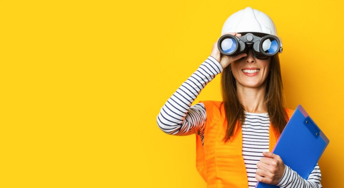 A woman wearing a hard hat and safety vest is looking through a pair of binoculars.