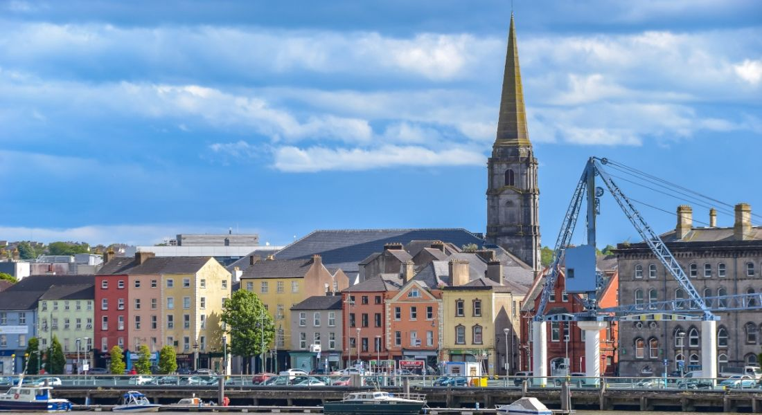 Waterford cityscape from across the River Suir. You can see a row of colourful buildings and a tall church steeple.