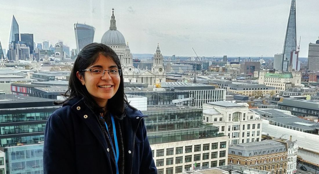 A woman stands against a wide city landscape with many tall buildings, smiling at the camera.