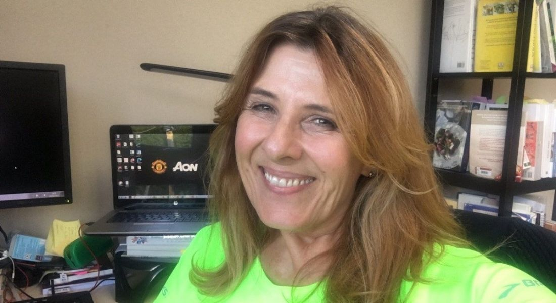 A woman wearing a bright green T-shirt sits away from a desk smiling at the camera. A laptop behind her displays the Aon logo.