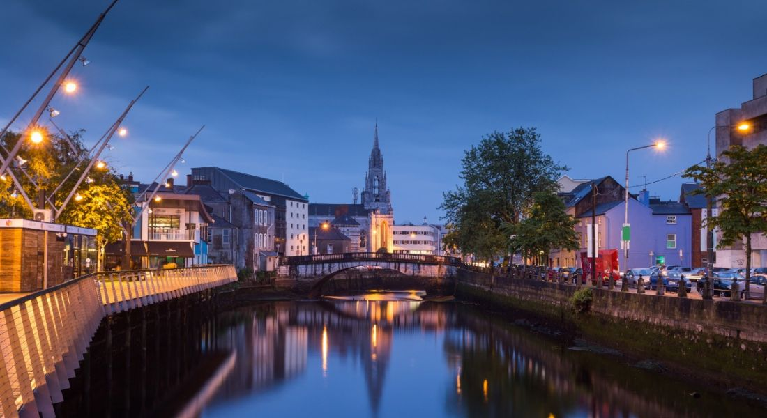The River Lee in Cork city at dusk, with buildings lit up either side of the docks.