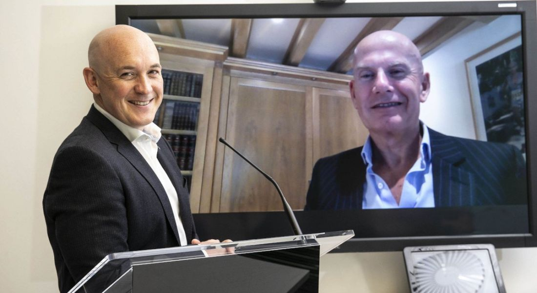 One man stands at a podium smiling at the camera while another man smiles from a television screen beside him.