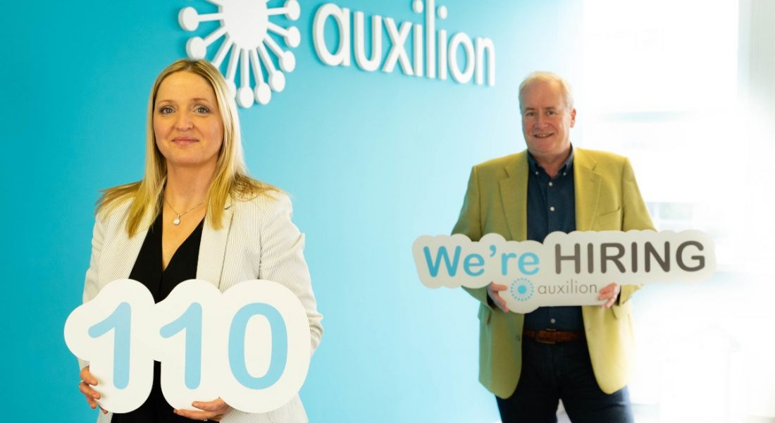A woman and a man stand a few metres apart beside a blue wall with a white Auxilion logo on it. They're holding signs - one that has the number 110 on it, and one that says 'We're hiring'.