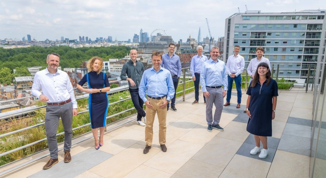 A group of people standing in a socially distanced formation on the rooftop of a London office.