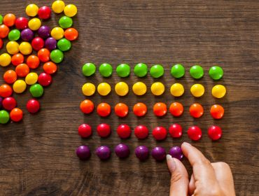 A hand takes different coloured sweets from a pile and puts them in perfect, matching lines, symbolising a perfectionist mindset.