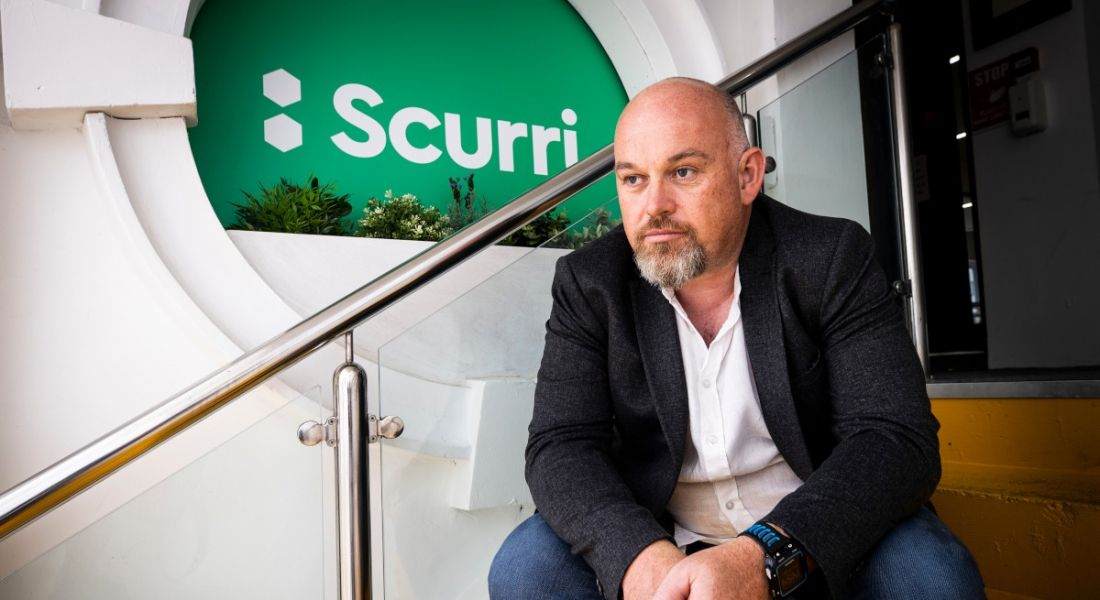 Scurri founder Rory O'Connor sits on a staircase next to a green Scurri logo.