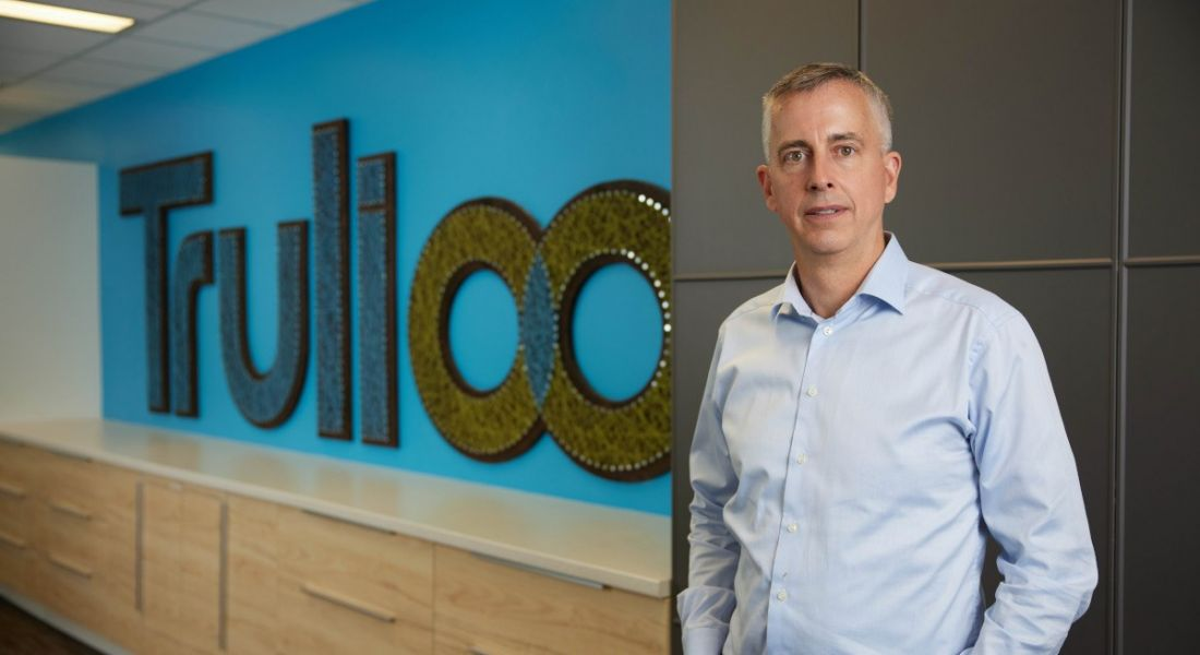A man in a shirt stands in an office in front of a sign that says Trulioo.