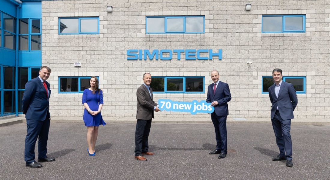 Four men and one woman stand outside an office building with the SimoTech logo on it. Two men hold a sign that says '70 new jobs'.