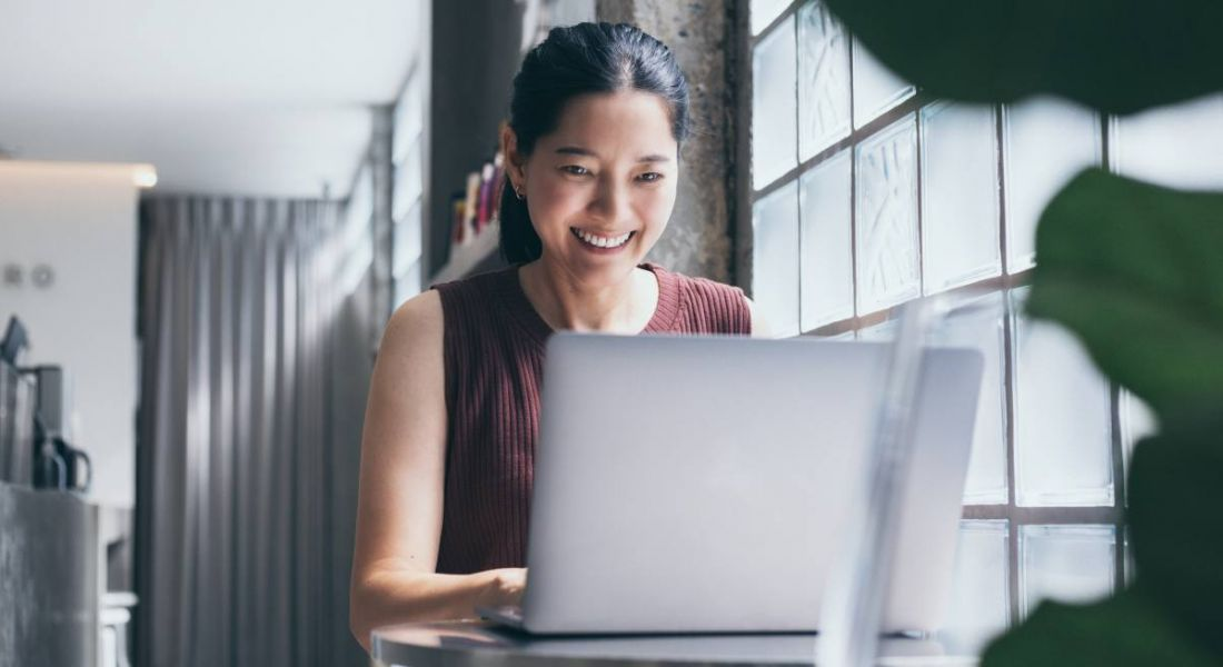 A young woman working on a laptop in a bright room by a window. She's smiling at the screen.