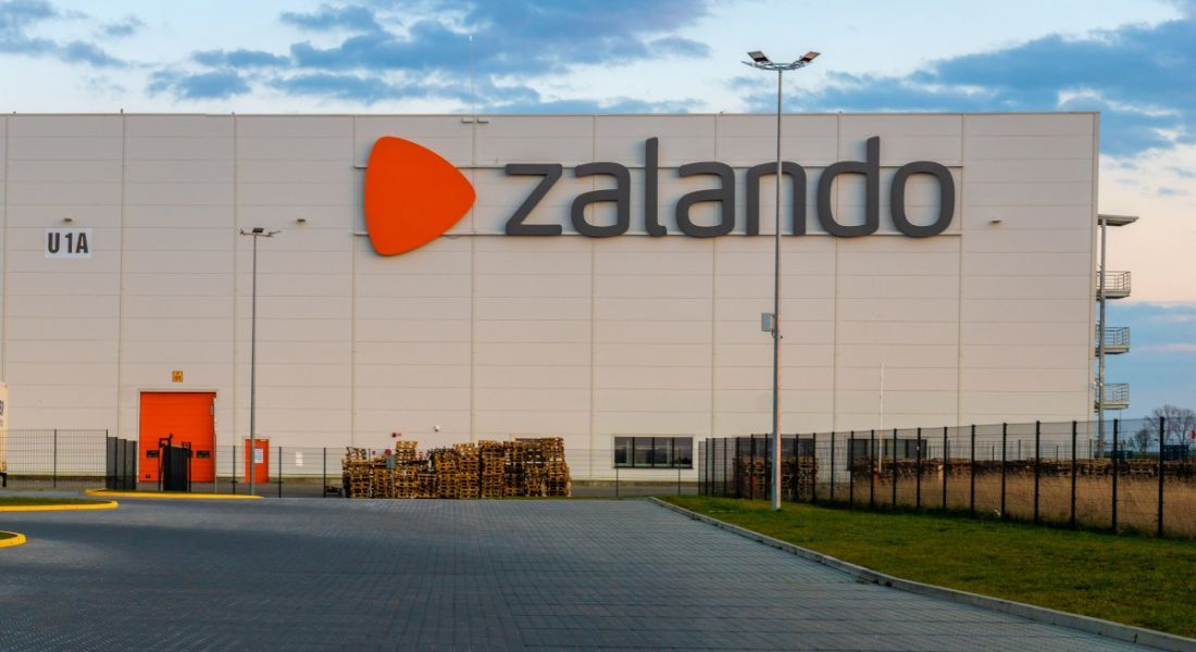 A large warehouse with the Zalando logo on the side against a blue sky at sunset.