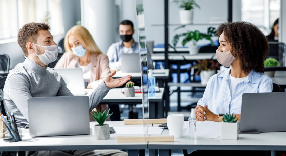 Four managers sit in an open-plan office wearing face coverings with protective screens between desks.