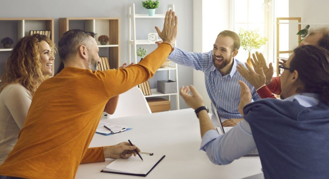 A group of people around a boardroom table cheering and high-fiving.