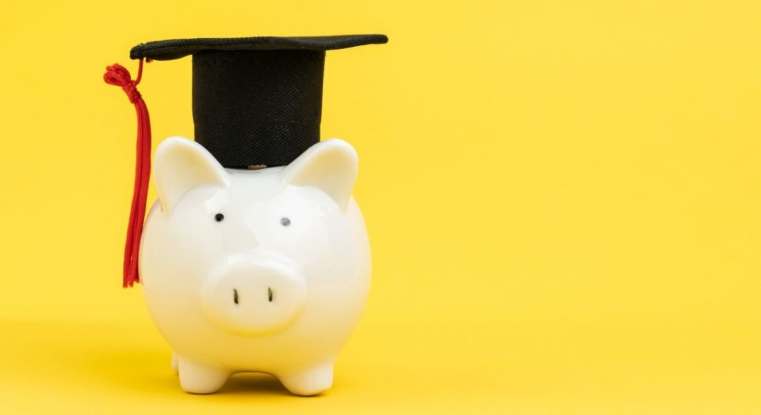 A white piggy bank wearing a graduation cap against a yellow background.