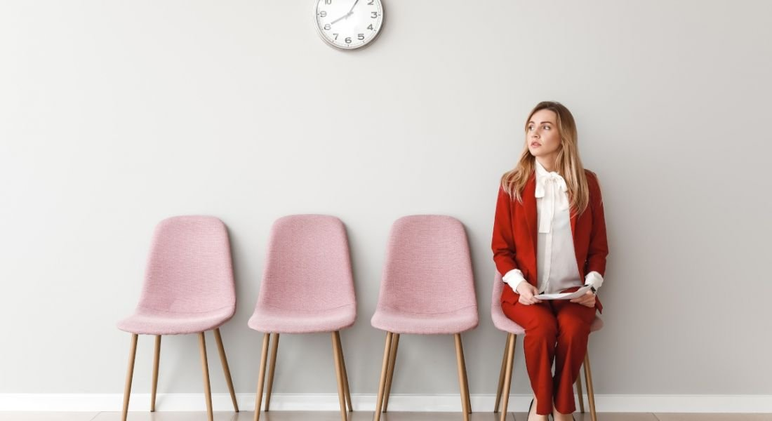 A woman in a red business suit sits at the end of a row of chairs nervously holding a CV before a job interview.