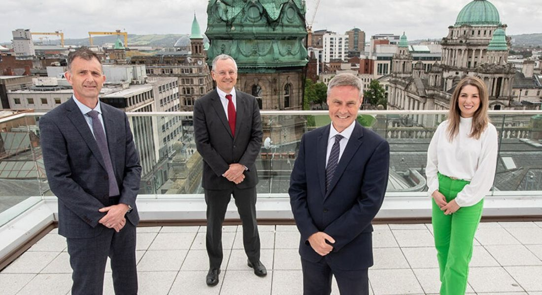 A group of people standing on the rooftop of a building in Belfast.