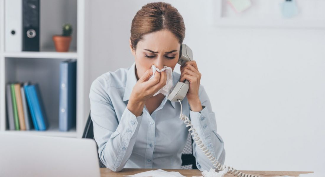 A woman sitting at her work desk using a phone while blowing her nose. Her desk is covered in used tissues.