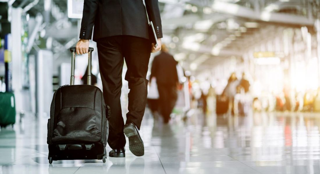 A man in a business suit walking through an airport wheeling a small suitcase behind him.
