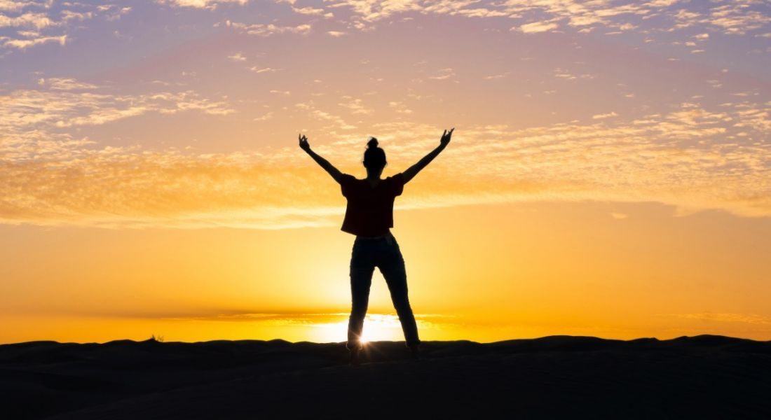 A silhouette of a woman standing with arms outstretched towards the sky at sunset.