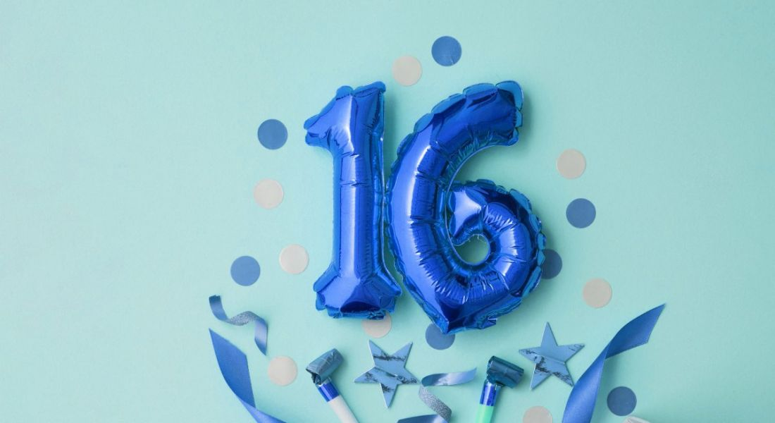 Two foil blue balloons spelling the number 16. It's surrounded by blue confetti against a mint green background.