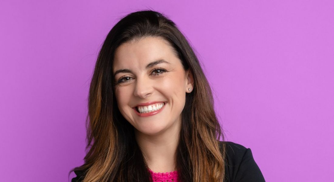 A close-up of Melanie Fellay, a woman with dark hair smiling at the camera against a bright purple background.