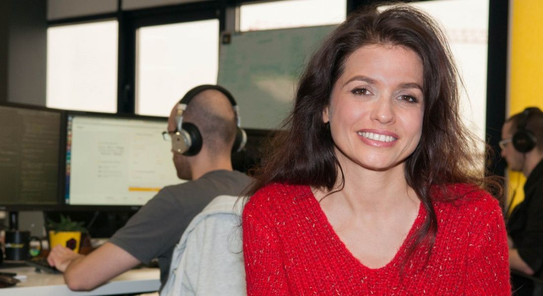 A woman wearing a red top is smiling at the camera while a man works on a laptop in the background.