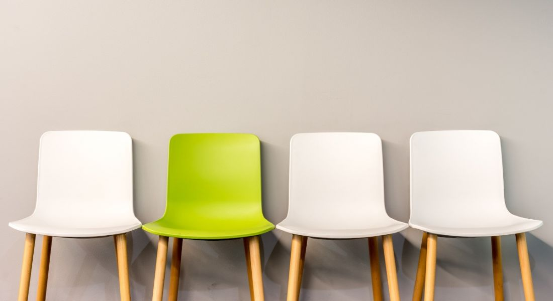 A row of chairs lined up for job interviews. Three of the chairs are white and one is lime green.