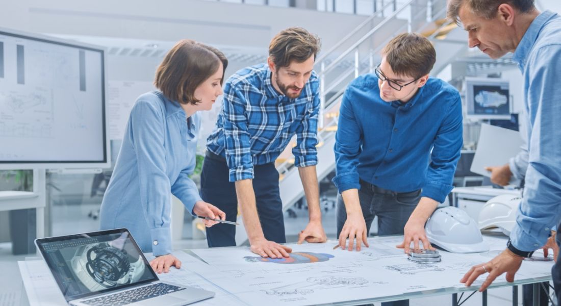 Four product designers gathered around a desk collaborating on a project.
