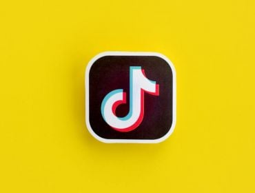 A paper logo for TikTok, which resembles a music note, on a bright yellow background.