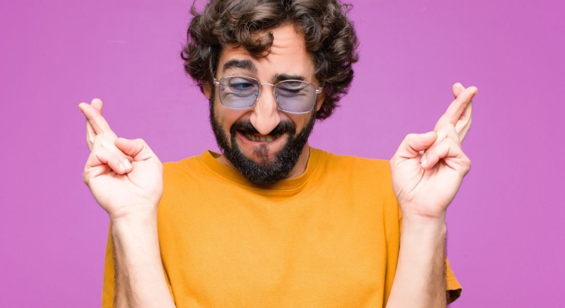 Bearded sun-glasses-wearing man smiles nervously and crosses his fingers in an exaggerated gesture.