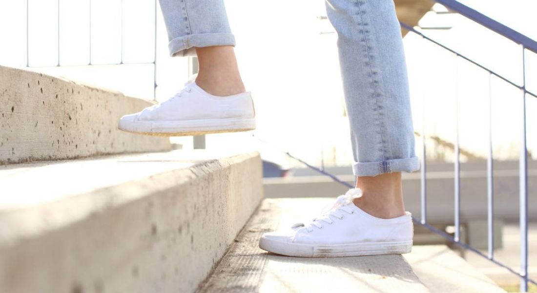 Close up shot of woman's legs as she climbs a concrete staircase. She is wearing ankle-length jeans and white plimsolls.