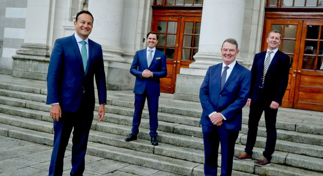 Four men in suits stand outside Government buildings.