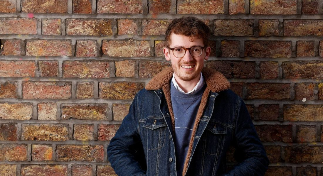 A headshot of Ben Butler, head of talent at Evervault, standing against a brick wall, smiling at the camera.