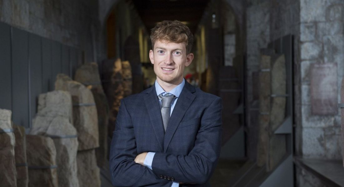 Conor Lyden of Trustap stands in a suit with arms crossed smiling at the camera.