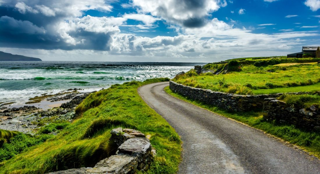 A winding Irish country road is shown. There is a small house on the right and the ocean is on the left of the road. There is a stone wall running alongside the road and there are fields of grass beyond the wall.