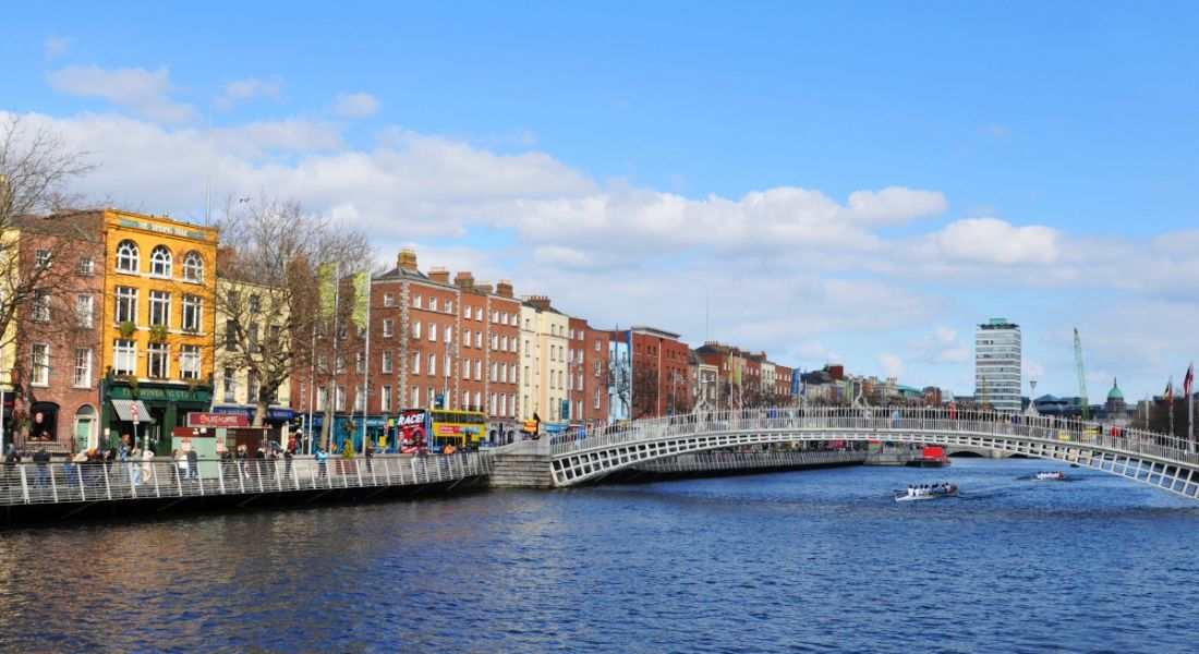 A wide shot of the River Liffey in Dublin with the Ha'penny Bridge in the centre of the photo on a sunny day.