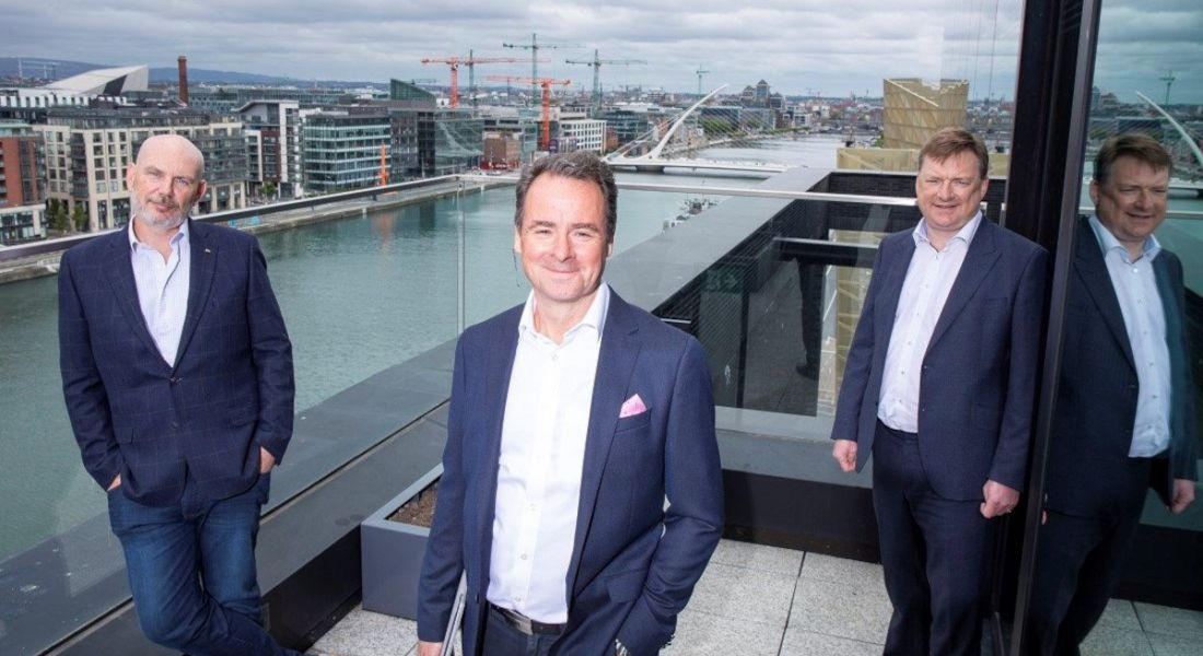 Three men stand on a balcony overlooking the Dublin docklands.