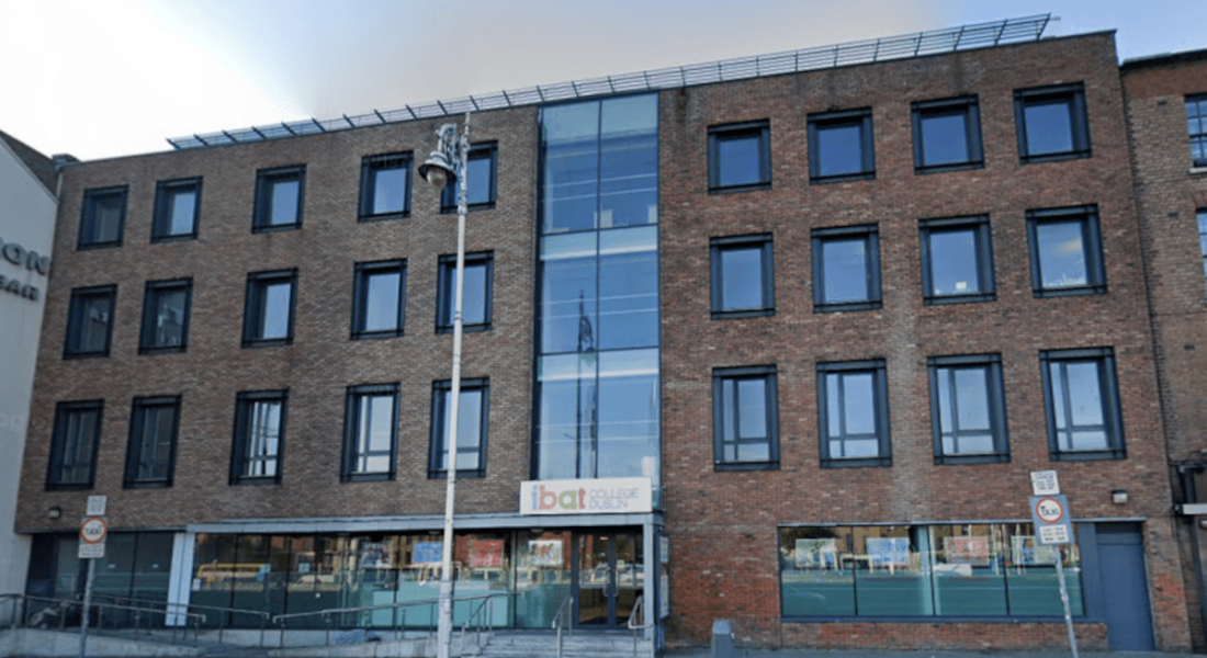 A view of IBAT College Dublin from across the street. It shows a large, brown brick building with 27 windows.