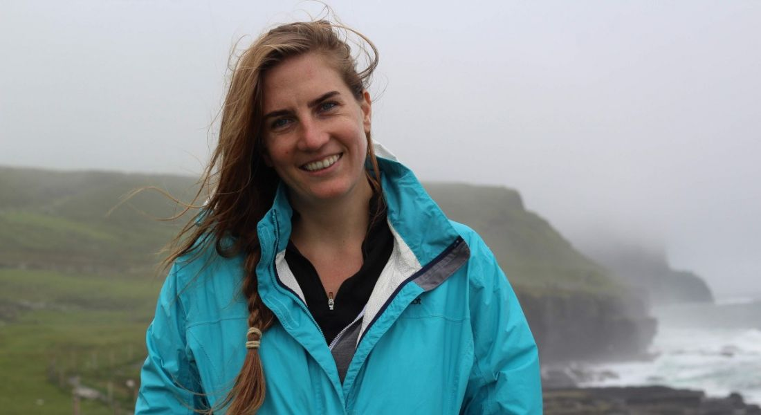 A young woman in a bright blue windbreaker stands on a hilltop on a windy, foggy day, smiling at the camera.