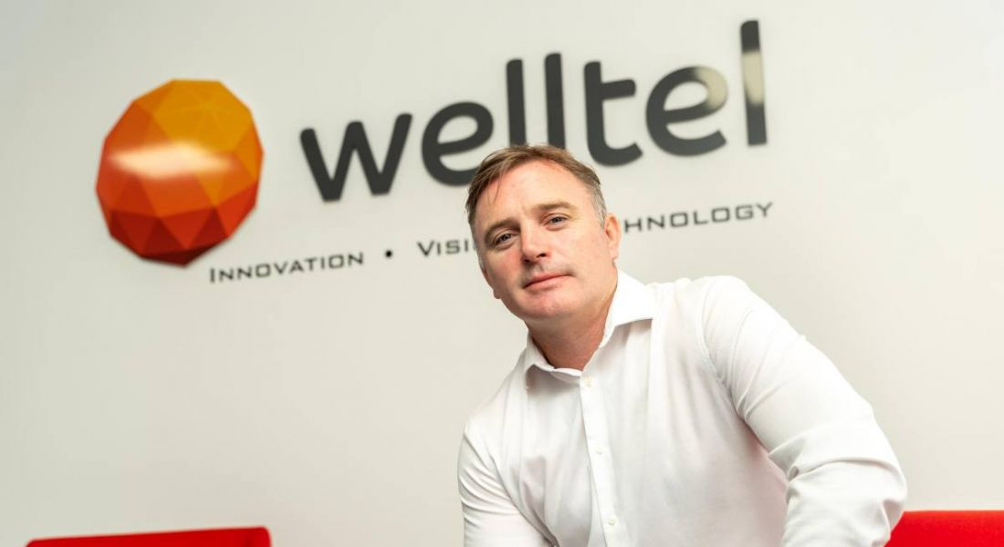 A man in a white shirt sits on a red chair. On the wall behind him is the Welltel logo.
