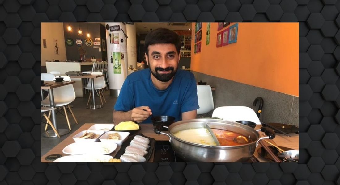 A man, Sachi Gowda, sits at a table in a restaurant with a variety of food in front of him. He is smiling at the camera.