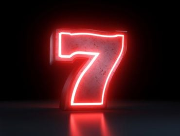 A large neon red number seven against a black background.