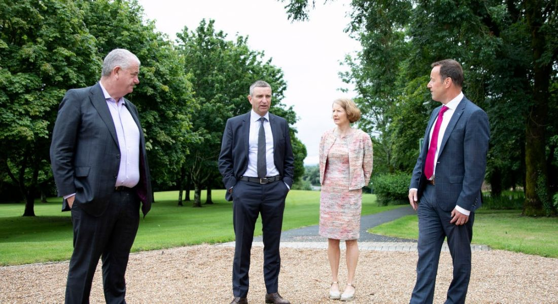 Three men and a women stand socially distanced while having a discussion outside. They are standing on a loose gravel path surrounded by green spaces and trees.