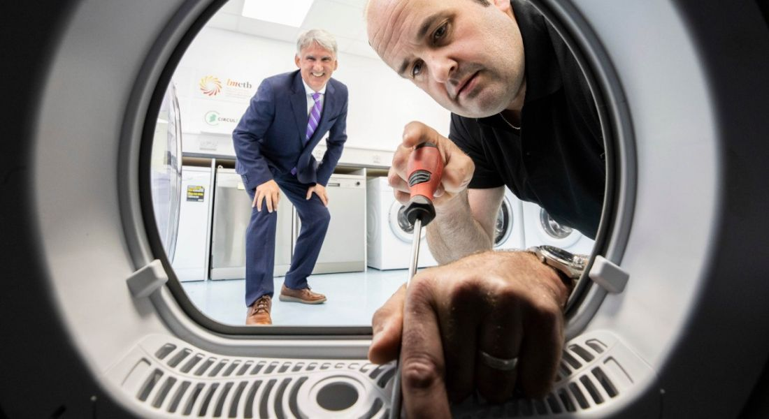 Leo Donovan, CEO of WEEE Ireland stands crouched behind Declan McElwaine, the owner of Electrical Appliance Services as he works on a washing machine with a screwdriver. The image is taken as if from inside the washing machine.
